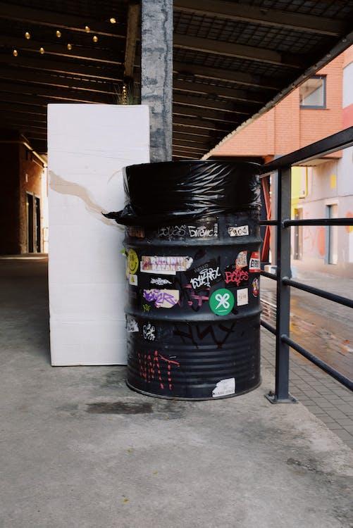 Black Plastic Trash Bin Beside Metal Railing