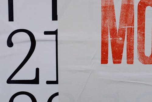 Closeup of letters and numbers printed on white banner placed on wall of modern building on street in city