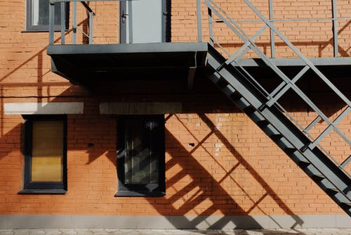 Brown Brick Building With Black Metal Window Frame and Stairs
