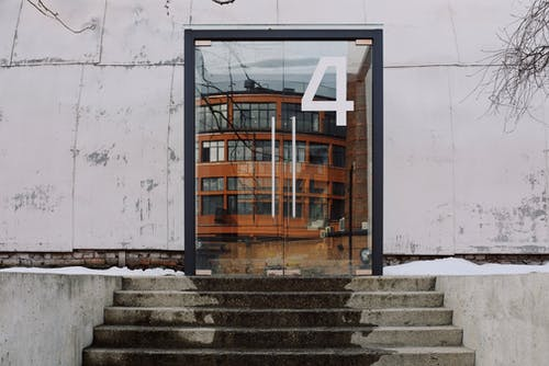 From below of modern building facade with number four on glass entrance door and stairs
