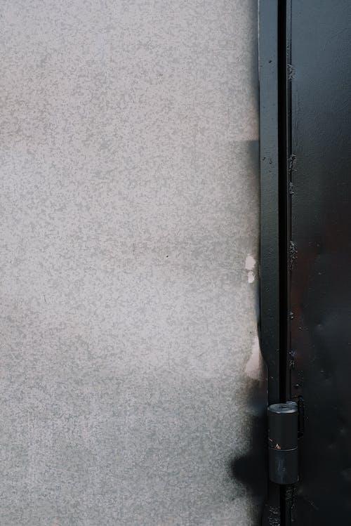 Metal door hinge and grungy wall