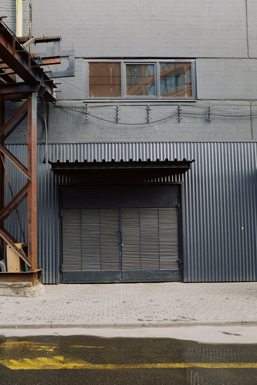 Exterior of black building with window and metal construction placed in industrial district of modern city outdoors roads with yellow lines