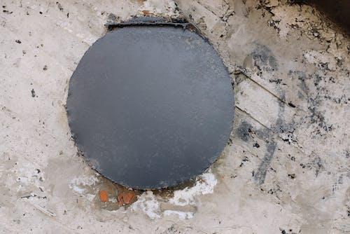 Black Round Round Plate on Gray Concrete Floor