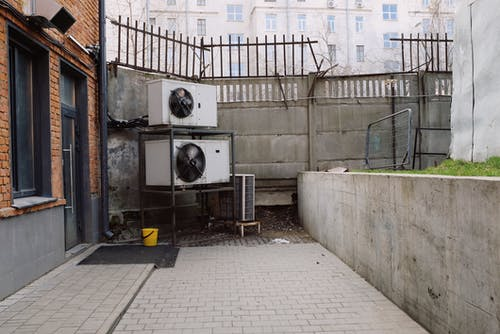 Air conditioning system located outside concrete shabby fence with metal barrier near industrial building from bricks and glass door