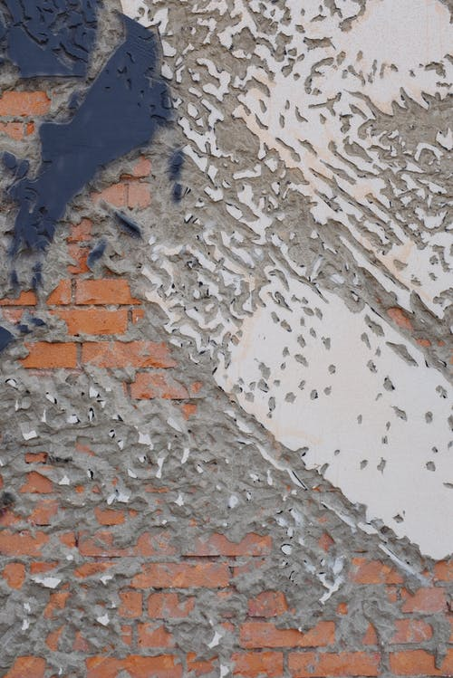 Bright abstract old wall with concrete and brick texture located in city outskirts district outside in daytime