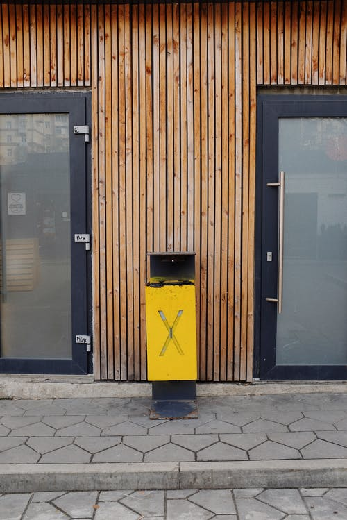 Bin on street pavement near glass door