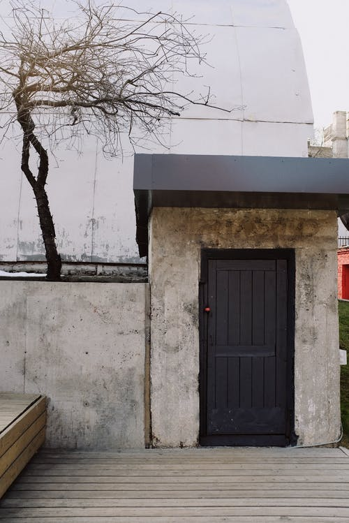 Black Wooden Door on White Concrete Wall