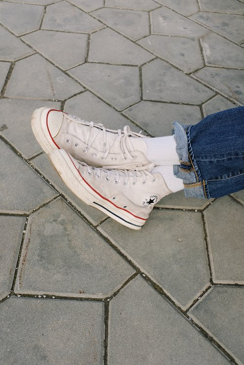 Person Wearing Denim Jeans and White Converse Sneakers