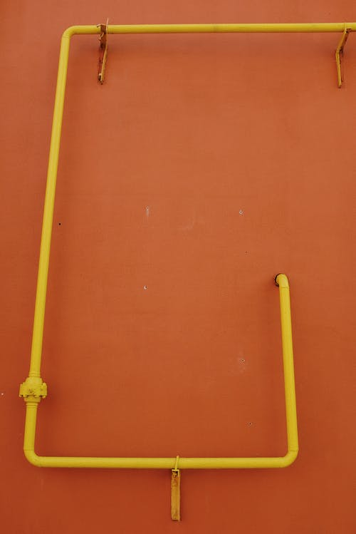 Yellow Pipes on Orange Wall