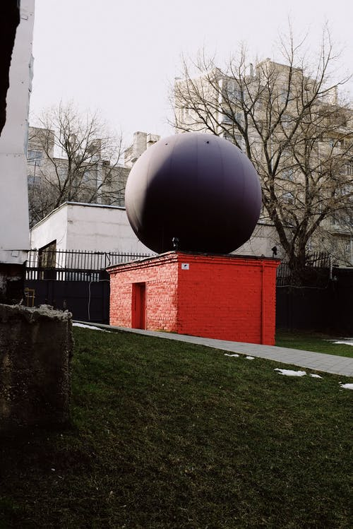 Gray Ball on Green Grass Field Near White and Red Building