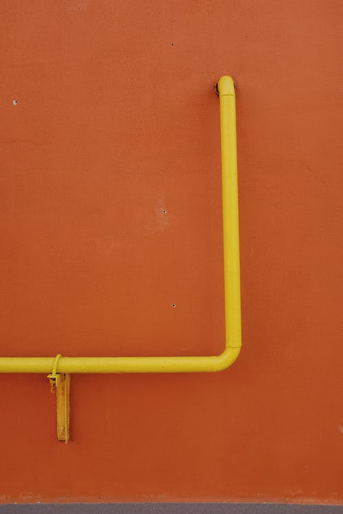 Yellow Metal Pipe on Orange Surface