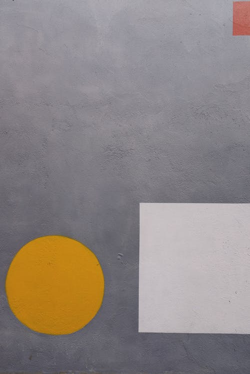 Yellow Circle and White Square on Gray Surface