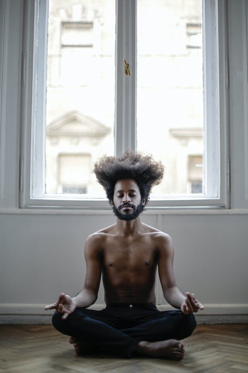 Topless Man Sitting Near Window Doing Yoga