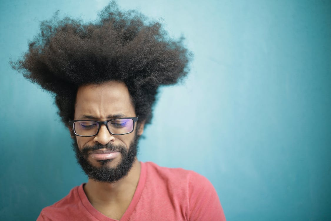 Young bearded ethnic male with creative Afro hairstyle wearing eyeglasses and pink t shirt looking down pensively thinking about trouble or question
