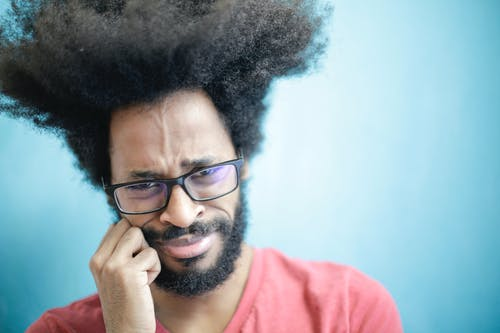 Suspicious young bearded ethnic male with creative Afro hairstyle wearing eyeglasses and pink t shirt touching cheek and looking at camera with uncertain or doubt expression