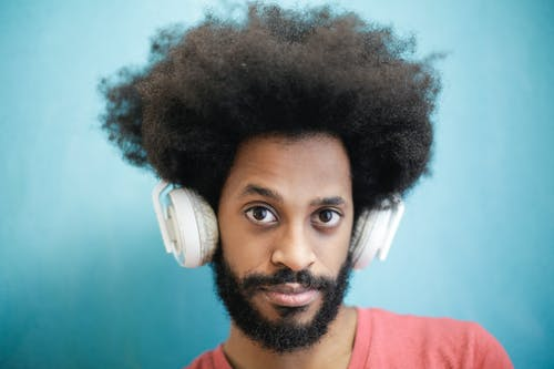 Content ethnic man in casual wear listening to music on blue background in studio