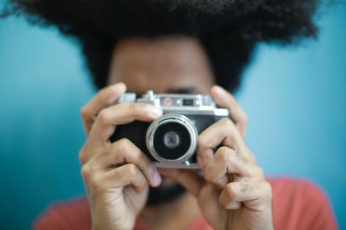 Young ethnic man using film photo camera on blue blurred background