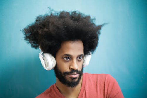 Content ethnic man in casual outfit using white headphones