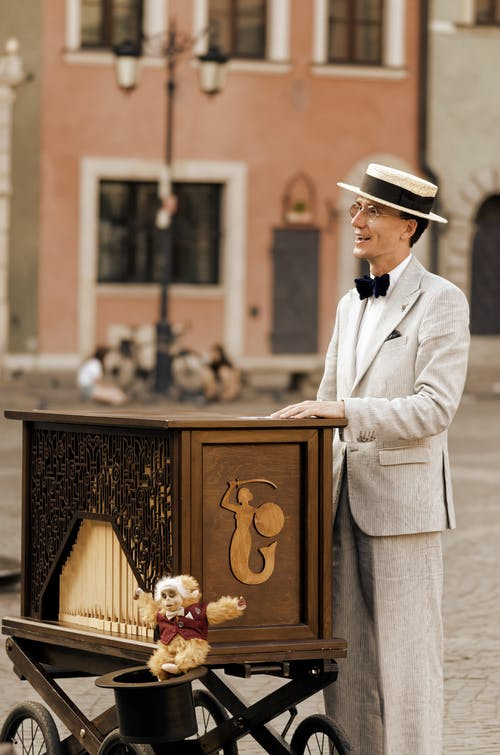 Man in White Suit Standing Beside Brown Wooden Table