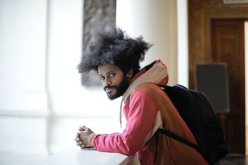 Man in Pink Sweater Wearing Black Backpack