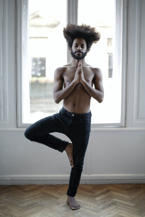 Topless Man in Black Pants Standing Near Window Doing Tree Pose