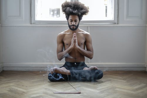 Topless Man in Black Denim Jeans Sitting on Floor Doing Meditation