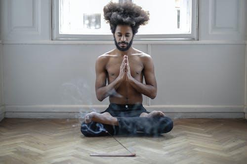 Topless Man in Black Denim Jeans Sitting on Floor Doing Meditation