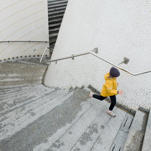 Girl in Yellow Jacket Running on the Staircase