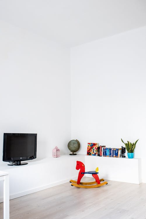 Black Flat Screen Tv on White Wooden Table and Red Rocking Horse