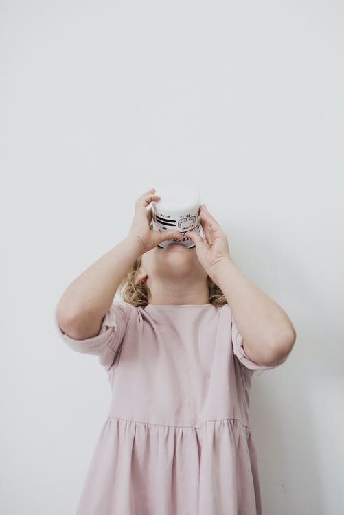 Adorable little girl drinking cup of milk