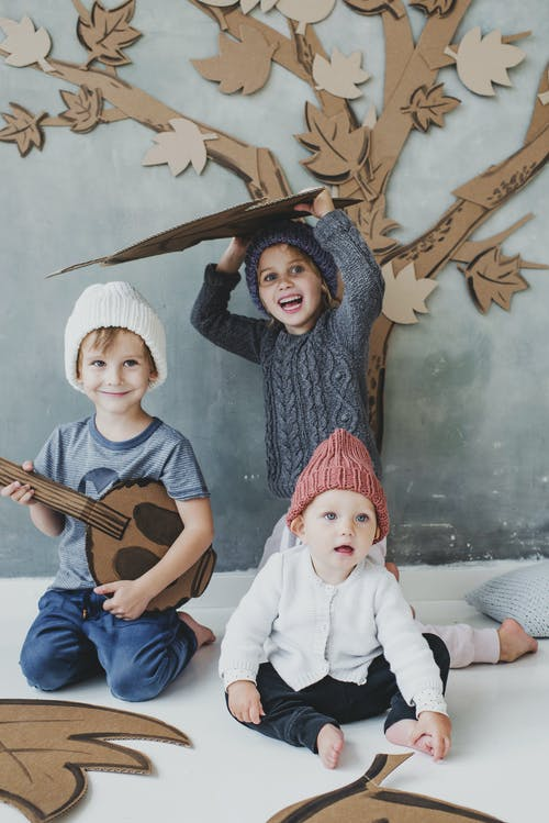 Children Sitting on Floor Playing with Cardboards