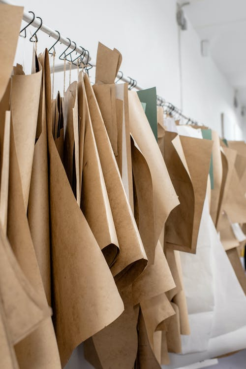 Set of sewing patterns on hangers inside tailor atelier or studio