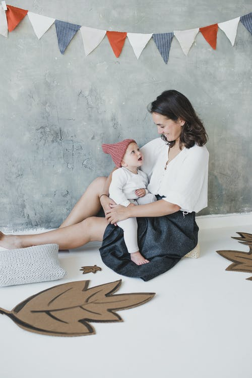 Woman in White Top and Black Skirt Sitting on a Pillow with Her Baby