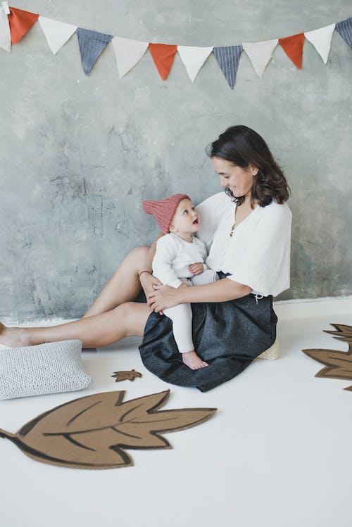 赤ちゃんと一緒に枕に座っている白いトップと黒いスカートの女性
