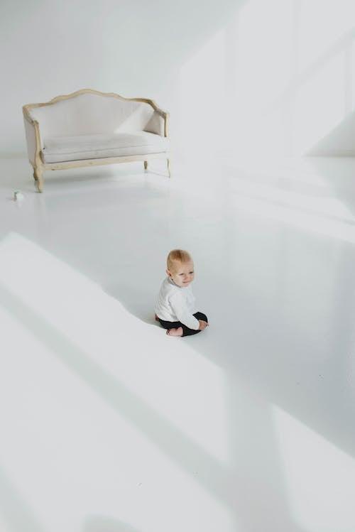 Baby Sitting on White Flooring