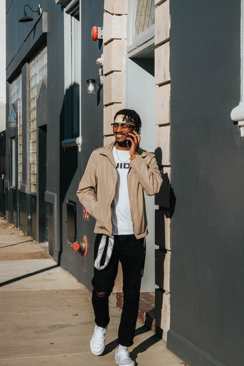 Man in Beige Jacket and Black Pants Standing on Sidewalk