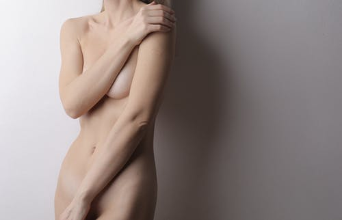 Nude Woman Covering Her Body With Her Hands