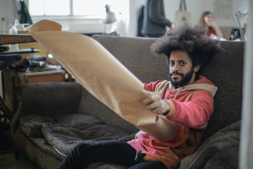 Man Sitting on a Couch Holding Brown Paper