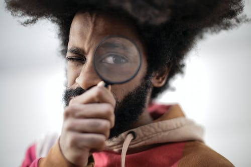 Person in Red and Brown Jacket Holding Magnifying Glass