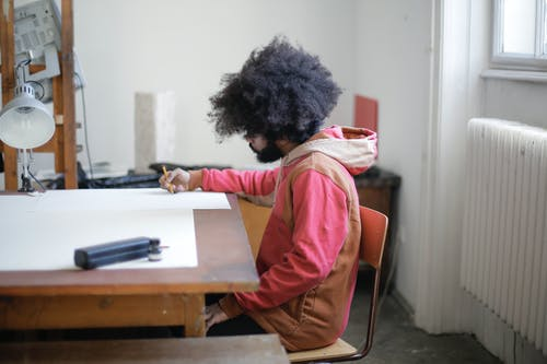 Man in Pink Jacket Sitting on Chair Drawing
