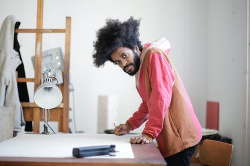 Young creative male painter drawing sketch in aged studio interior