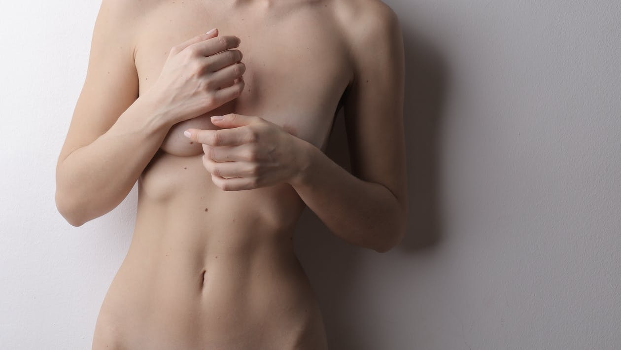 Topless Woman With Both Hands on Her Chest
