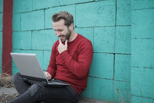 Man in Red Long Sleeve Shirt and Black Denim Jeans Sitting on the Ground Using Laptop