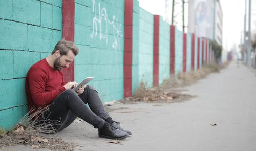 Man in Red Shirt and Black Pants Sitting on Concrete Ground Using Ipad