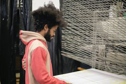 Focused young ethnic designer working with white material in workshop