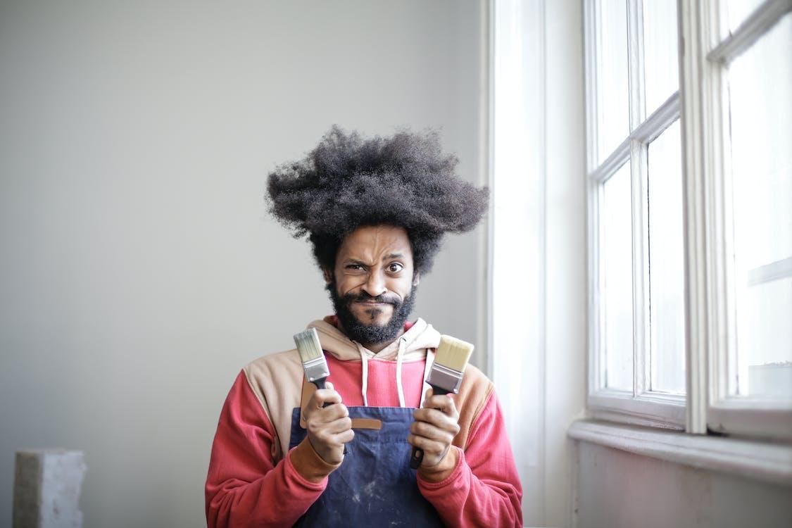 Man Holding Two Paintbrushes