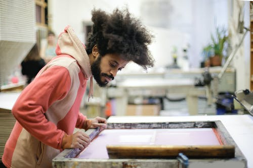 Side view of creative ethnic male in casual hoodie standing near workbench and working with wooden frame in creative workshop
