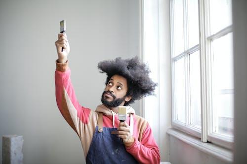 Man Having Fun Holding Two Paintbrushes