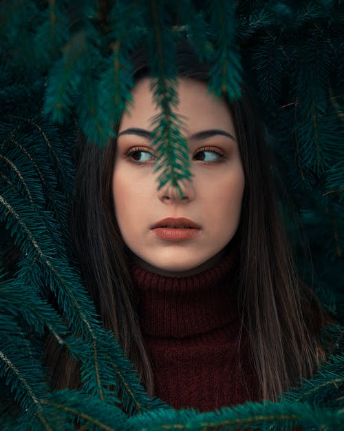 Beautiful Woman Behind Green Leaves