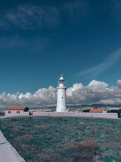 White Concrete Lighthouse Under Blue Sky